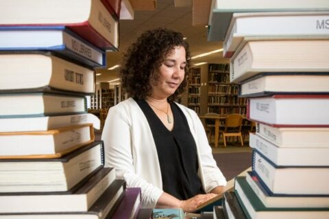 asian lady seen through two stacks of library books