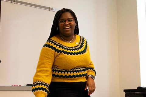 female, African American student wearing yellow and black sweater